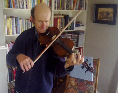 Dwight Walker teaching violin in a student's home in Orange in 2012